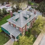 light grey shingled roof aerial view brick mansion 2