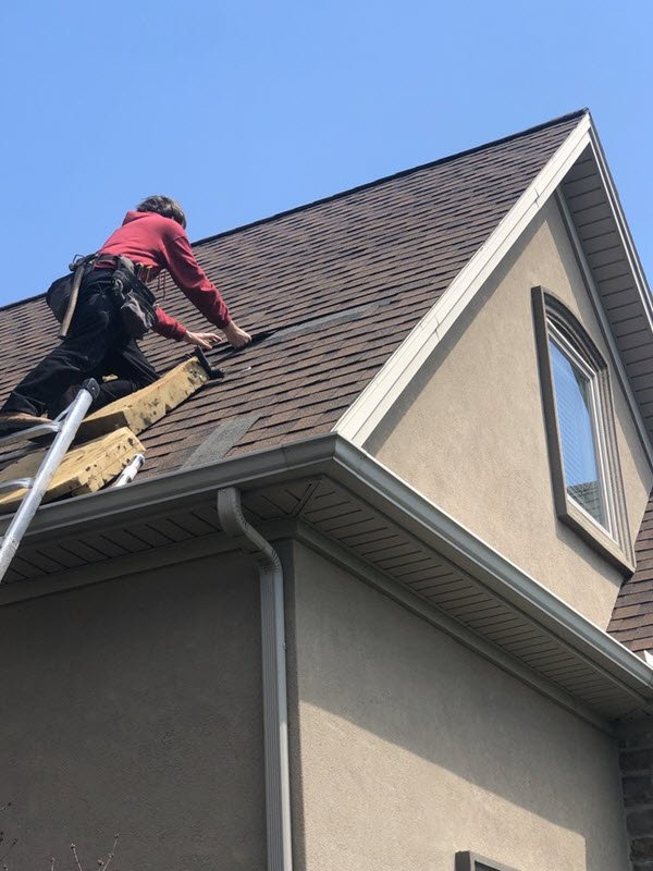 roofer repairing shingles medium